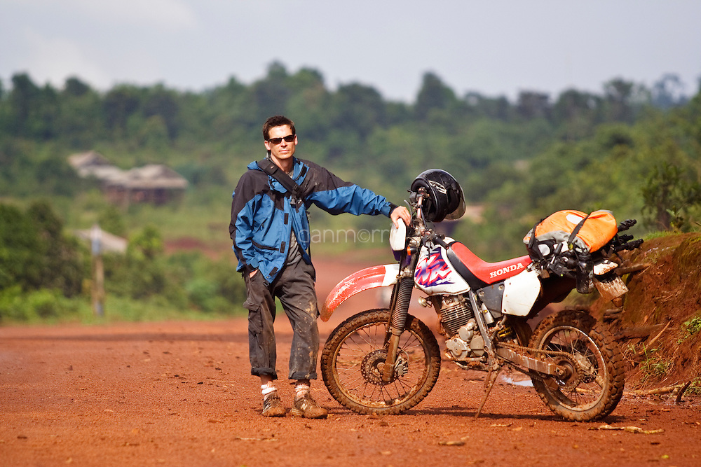 Tourist rides motorcycle through jungle in Mondulkiri province, Cambodia