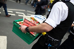 © Licensed to London News Pictures. 07/10/2019. London, UK. A Police officer removes a crate of Tea Bags from an Extinction Rebellion Roadblock on Millbank . Photo credit: George Cracknell Wright/LNP