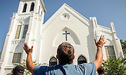 Robin Goolsby prays outside the Emanuel A.M.E. Church during a morning service four days after a mass shooting that claimed the lives of it's pastor and eight others, Sunday, June 21, 2015, in Charleston, S.C. (AP Photo/Stephen B. Morton)
