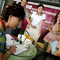 "BEIJING, 29.July : doctor Shi Sanba (L) shows facial features that can be changed in her notebook to a mother (R) and her teenage daughter (2nd right) while other potential customers watch  in Beijing, July 29, 2004, in China. Doctor Shi works in a hospital that specializes in plastic surgery which gradually is becoming big business in China's capital. Shi's hospital has been flooded with teenage patients ever since she started to offer ""special summer reductions"" for students. Yang Yuan, the would-be model who'd  had plastic surgery and had sued the organizer a model contest after being banned from the contest, also was treated in Shi's hospital ...Whereas in Mao Zedong's China, even pigtails were seen as a sign of vanity (and had to be cut off) , nowadays, urban Chinese women seek about every means in order to distinguish themselves from the masses.  This year Beijing will organize the worl'd first beauty pageant for women had had plastic surgery..."