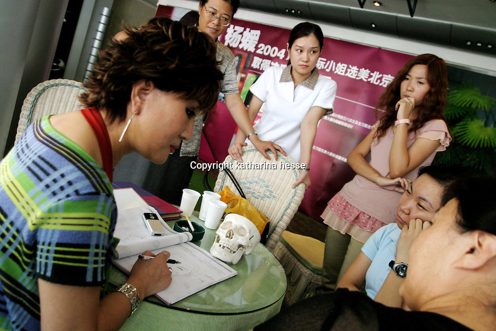 """BEIJING, 29.July : doctor Shi Sanba (L) shows facial features that can be changed in her notebook to a mother (R) and her teenage daughter (2nd right) while other potential customers watch  in Beijing, July 29, 2004, in China. Doctor Shi works in a hospital that specializes in plastic surgery which gradually is becoming big business in China's capital. Shi's hospital has been flooded with teenage patients ever since she started to offer """"special summer reductions"""" for students. Yang Yuan, the would-be model who'd  had plastic surgery and had sued the organizer a model contest after being banned from the contest, also was treated in Shi's hospital ...Whereas in Mao Zedong's China, even pigtails were seen as a sign of vanity (and had to be cut off) , nowadays, urban Chinese women seek about every means in order to distinguish themselves from the masses.  This year Beijing will organize the worl'd first beauty pageant for women had had plastic surgery..."""