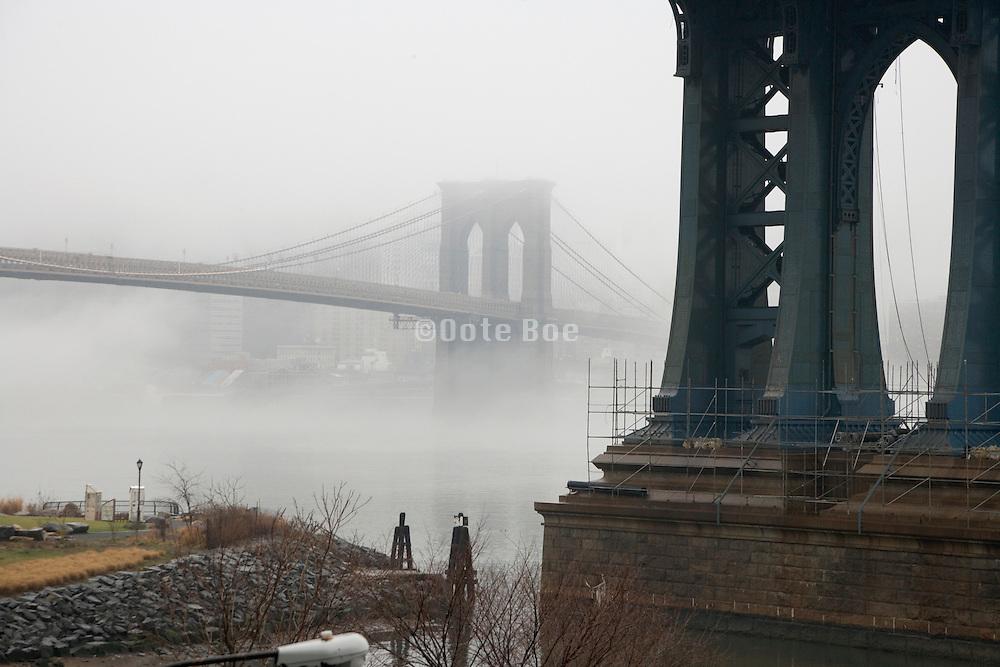 Brooklyn Bridge with Manhattan Bridges pillar in the foreground during a morning fog