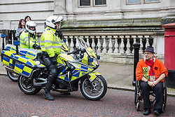 London, UK. 7 October, 2019. A climate activist in a wheelchair from Extinction Rebellion temporarily blocks Birdcage Walk in front of two Metropolitan Police motorcyclists on the first day of International Rebellion protests to demand a government declaration of a climate and ecological emergency, a commitment to halting biodiversity loss and net zero carbon emissions by 2025 and for the government to create and be led by the decisions of a Citizens' Assembly on climate and ecological justice.
