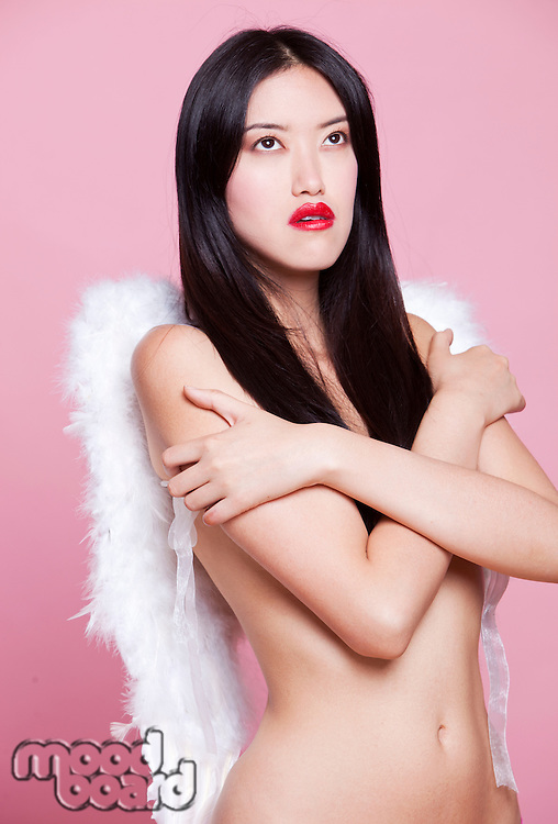 Contemplative young woman with angel wings against pink background