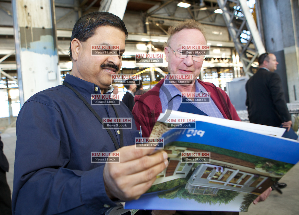 Sam Kumar and Bill Tuikka, from the City of Vallejo look at a brochure as  Blu Homes opens their West Coast factory on Mare Island in Vallejo, California Dec. 1, 2011.  Over 400 guests attended a ribbon cutting ceremony at the 250,000-square-foot facility.