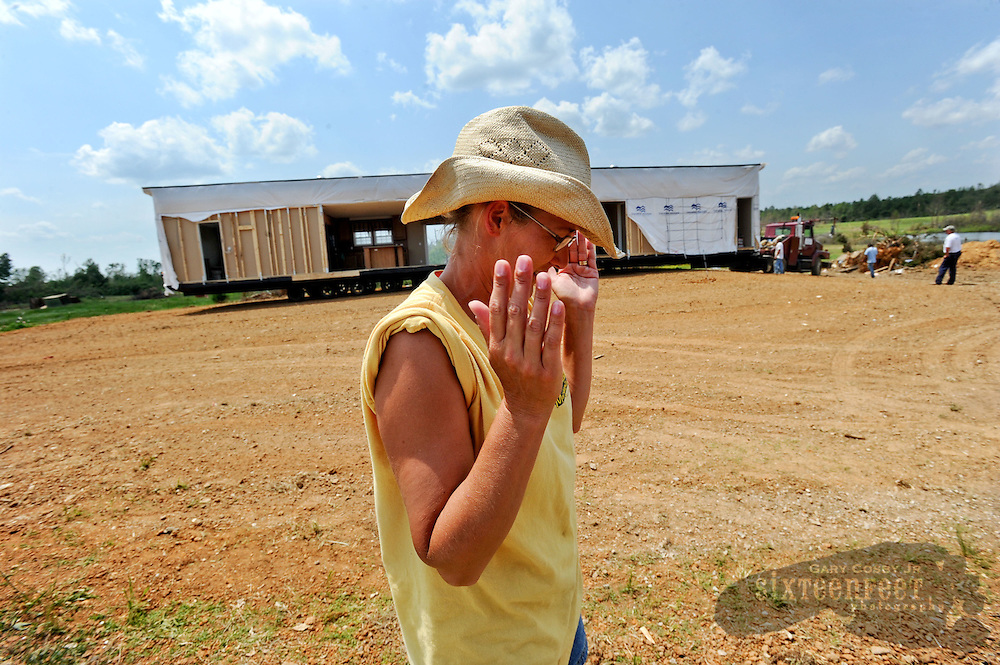 Daily Photo by Gary Cosby Jr...Robbie and Kim Stewart took delivery of their new mobile home Thursday replacing their house destroyed in the April 27 tornado.  Kim Stewart rejoices as the new home is delivered.