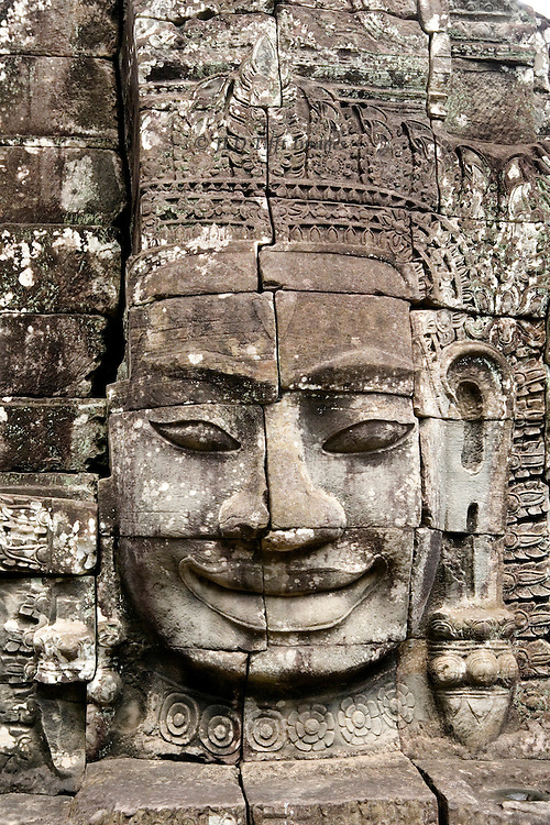 Angkor Thom, Bayon, four faced towers of the temple.  The giant heads, each facing a cardinal compass point as protection, may be portraits of Jayavarman VII, the king who built the temple XII century.  This head wears a broad, satisfied smile.