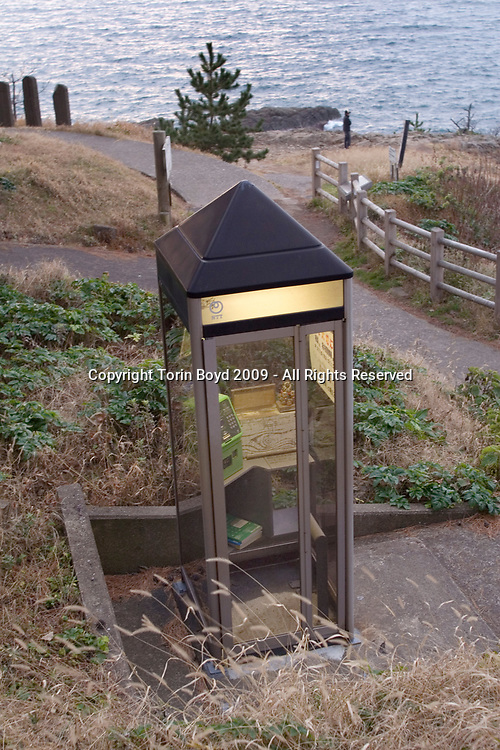 Nov. 27, 2009, Sakai City, Japan: This is a special telephone booth installed close to to where many suicides occur along the rocky cliffs of Tojinbo, a popular tourist spot on the Japan Sea coast. This booth has a sign large sign with a number to call for help, as well as a donation box with ten yen coins and telephone cards for distressed individuals to use as a last resort to save themselves. Located in Sakai City, Fukui Prefecture, the scenic Tojinbo area known for it's coastal beauty, seafood and onsen hot springs resorts now adds suicide as a reason to come here. In 2008 twenty suicides occurred here, but this figure varies between Sakai City officials and a suicide help group dedicated to preventing suicides here, and also responsible for this special telephone booth. Called Kokoro ni Hibiku Bunshu Henshukyoku, this NPO founded in 2004 by retired policeman Yukio Shige, who along with a group of volunteers patrols the cliffs on a daily basis to deter those contemplating jumping to their deaths. According to Shige, age 65, in the past five years since he founded his NPO, he is responsible for talking 222 people out of killing themselves. But even with Shige's efforts, the deaths here continue and as of late November, 2009, the current number of annual suicides at Tojinbo stands at thirteen. Japan has one of the highest suicide rates in the world and 2009 may surpass the record 34,427 deaths that occurred here in 2003. This increase is though to be a result of the Japanese recession which has been worsened by the global economic downturn. Depression is the number one cause for suicide in Japan, followed by illness and debt. Photo by Torin Boyd.