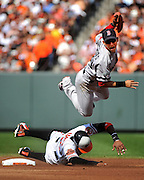 Boston Red Sox shortstop Jose Inlesias jumps over Baltimore Orioles Adam Jones as he turns a double play at Orioles Park at Camden Yards in Baltimore, Maryland.