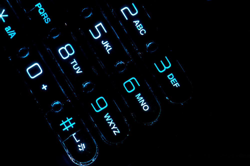 Close up view of a cell phone keypad backlit.