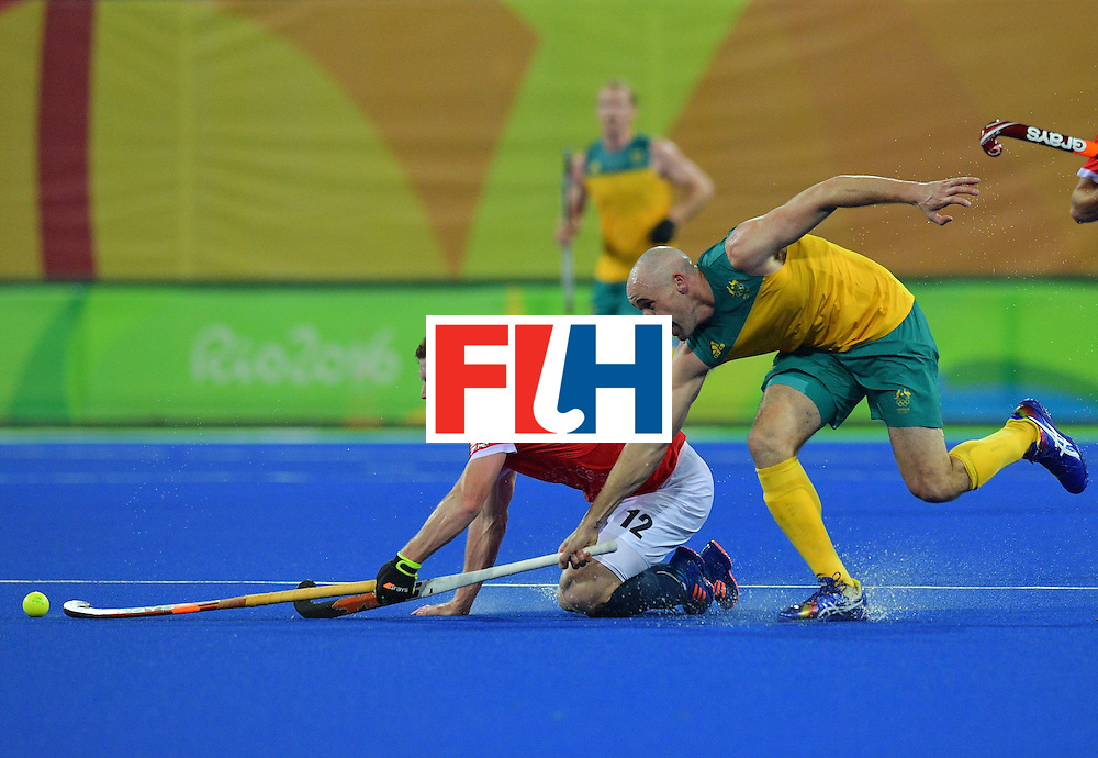 Australia's Glenn Turner and Britain's Michael Hoare chase the ball during the men's field hockey Britain vs Australia match of the Rio 2016 Olympics Games at the Olympic Hockey Centre in Rio de Janeiro on August, 10 2016. / AFP / Carl DE SOUZA        (Photo credit should read CARL DE SOUZA/AFP/Getty Images)