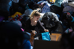 London, June 15th 2017. Mountains of food and clothing donated to the many people who have lost everything and been made homeless in the Grenfell Tower fire of June 14th, by generous Londoners are categorised and stored on a basketball court at the Westway Sports Centre and other locations near to the scene of the fire. PICTURED: A volunteer opens a newly arrived bag of donated goods.