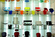 Colourful design chairs to sell in a rack shop.
