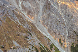 Constantine Metal Resources Ltd. of Vancouver, British Columbia along with investment partner Dowa Metals &amp; Mining Co., Ltd. of Japan is exploring a potential site for a mine on the steep mountain slopes shown in this photo. This area above Glacier Greek known as the Palmer Deposit, is located near mile 40 of the Haines Highway.<br /> <br /> The minerals that Constantine&rsquo;s drilling explorations have found are primarily copper and zinc, with significant amounts of gold and silver. Exploratory drilling to refine the location and mineral amounts are the current focus of the company.<br /> <br /> If approved and developed, the mine, near Haines, Alaska would be an underground mine. Besides the actual ore deposits, having the nearby highway access for transporting ore to the deepwater port at Haines is also attractive to Constantine. The Haines Highway can be seen in photo on the right.<br /> <br /> Support for a large scale mine such as the Constantine project is divided among residents of Haines, a small community in Southeast Alaska 75 miles northwest of Juneau. The community&rsquo;s needed economic boost from jobs, development and other mine support that a large-scale mine brings is tempting to some. To others, anything that might put the salmon spawning and rearing habitat and watershed resources at risk is simply unimaginable and unacceptable. Of particular concern is copper and other heavy metals in mine waste leaching into the Klehini River (shown) and the Chilkat River 14 miles downstream. Copper and heavy metals are toxic to salmon and bald eagles.<br /> <br /> The Chilkat River chum salmon are the primary food source for one of the largest gatherings of bald eagles in the world. Each fall, bald eagles congregate in the Alaska Chilkat Bald Eagle Preserve, located only three miles downriver from the area of current exploration.