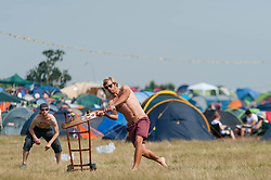 © Licensed to London News Pictures. 18/07/2014. Southwold, UK.   Festival goers play cricket on a hot sunny morning at the campsite at  Latitude Festival 2014 Day 1. Today is expected to be the hottest day of the year with temperatures forecast to reach 32 degrees centigrade.   Latitude is an British annual music festival.  Photo credit : Richard Isaac/LNP