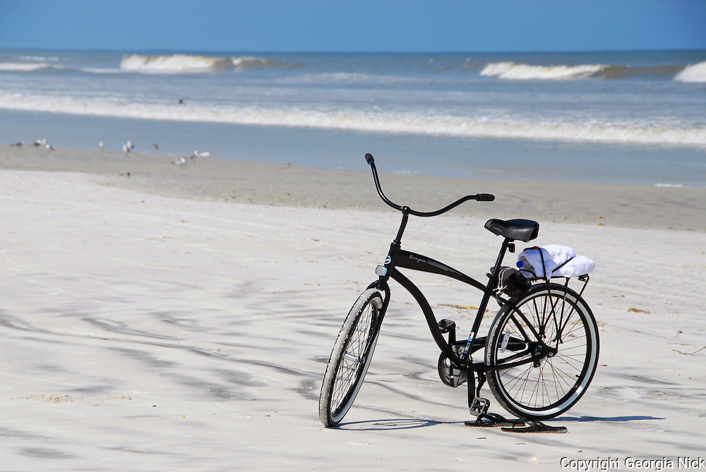 Beach Bike. A black bicycle standing near the dunes on the beach in Anastasia State Park, St. Augustine, Florida. The bicycle has a towel, water bottle and beach supplies attached on back. Flip flops left on the sand tell the story of someone out for a late summer swim on a beautiful Florida afternoon.