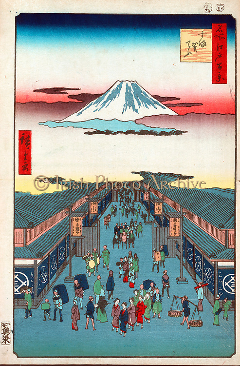 Suroga-Cho: from  'One Hundred Famous View of Edo', 1856.  Utagawa Hiroshige (1797-1858) Ukiyo-e artist. Street scene in Tokyo, Japan, with the sumit of Mount Fuji seemingly floating in the clouds.  Pedestrians Men Women Porters