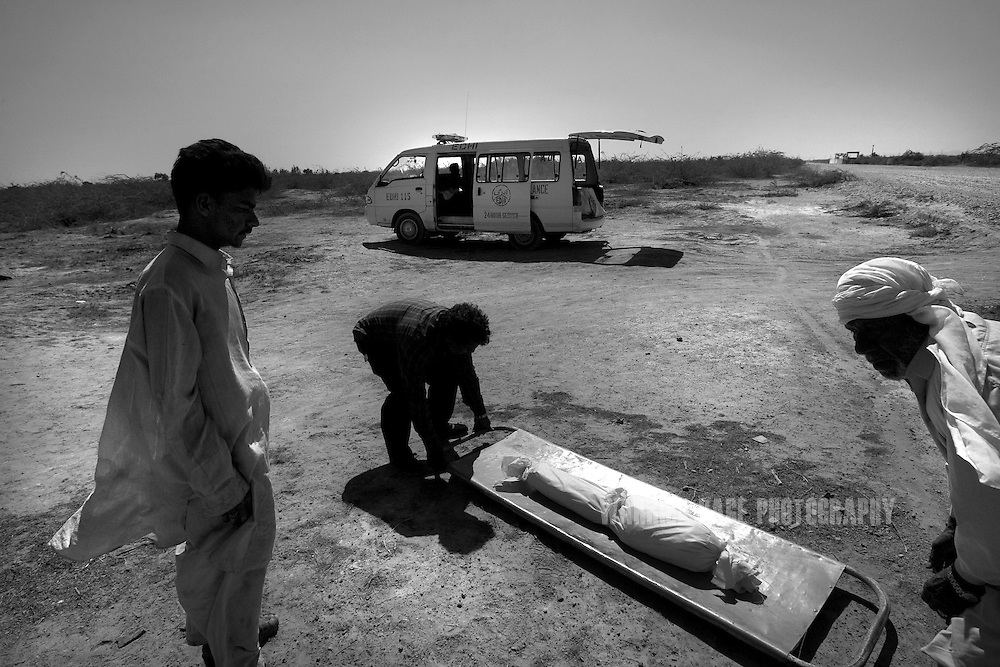 KARACHI, PAKISTAN - MARCH 6: Gravediggers at the Edhi cemetery carry the body of Tahira, 4, an Edhi orphan who died of respiratory complications, from an ambulance to a plot on March 6, 2008 in Karachi, Pakistan. The gravediggers prepare several graves in advance per day in preparation for the inevitable number of unclaimed bodies that the Edhi foundation provides a proper Muslim burial for. All graves are numbered and files kept at head office in the event of family members seeking to find the disappeared. The Edhi Foundation urges women give up unwanted children rather than abandon or kill in order to cover up children conceived out of wedlock, or through rape. The Edhi Foundation orphanages represent a microcosm of Pakistan's absolute poverty where children are its first casualty, tragedy and hope collide on a daily basis, and life and death are in constant flux existing only rooms apart. Pakistan is a country more than a third of it's population live in absolute poverty. As world attention fixates on Pakistan's ongoing political turmoil, generations of children are being abandoned due to Pakistan's spiraling poverty and growing instability. Some are born out of wedlock - a major social taboo - others discarded due to physical and mental disabilities, but nearly all are abandoned due to poverty. Boys and girls alike are abandoned every year, found in dumpsters mauled by rats and dogs, or left to fend for themselves on the streets of Karachi's sprawling and unforgiving metropolis. The lucky ones find their way to the Edhi Foundation orphanages. . (Photo by Warrick Page)