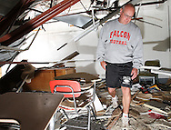 Ed Thomas, of Parkersburg, a teacher and football coach at Aplington-Parkersburg High School walks through his classroom in Parkersburg, Iowa on Wednesday June 4, 2008. Half of the roof in the classroom collapsed from the tornado. (Stephen Mally for the New York Times)