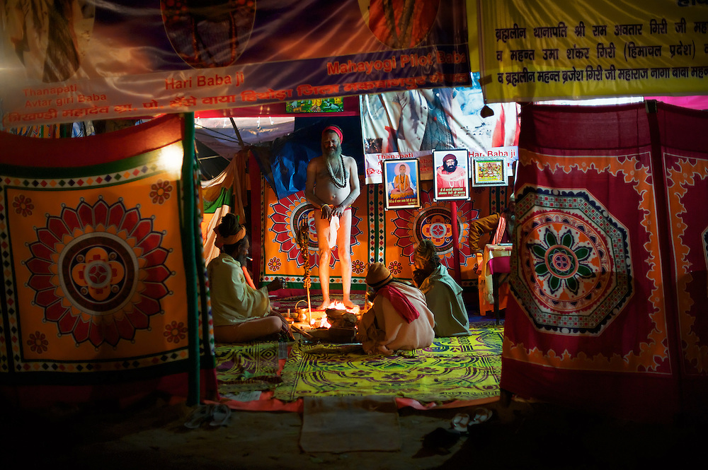 Hari Baba Ji standing and some other Naga babas sitting around the dhuni in Mahayogi Kapil Adwait's (Pilot Baba) tent in Juna Akhara during the Kumbh Mela in Haridwar, 2010. Naga Sadhus belong to the Shaiva sect, they have matted locks of hair and their bodies are covered in ashes like Lord Shiva.<br />