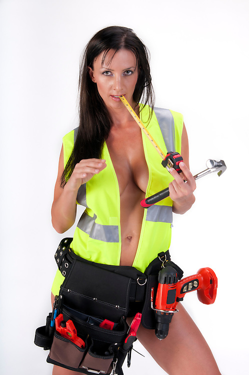 Very sensual woman with safety vest and tool. All logos removed.