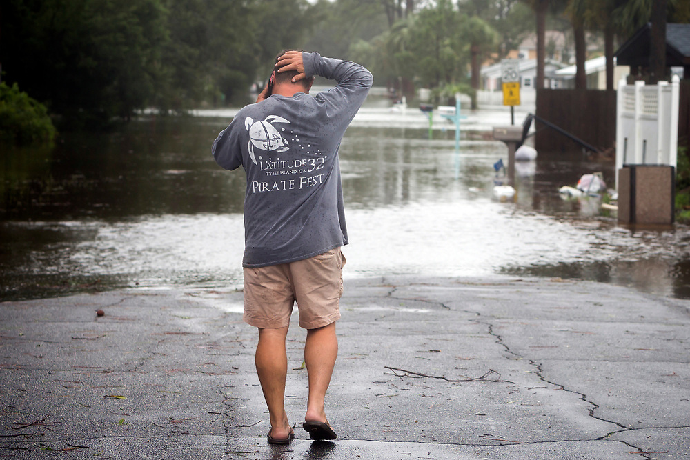 Joey Spalding reacts as he talks to friend about his flooded house, Monday, Sept., 11, 2017, on Tybee Island, Ga. Spalding just finished repairing his house from nine inches of water after Hurricane Matthew past the island last year. He said the Tropical Storm Irma brought three feet of storm surge into his living room today.  (AP Photo/Stephen B. Morton)