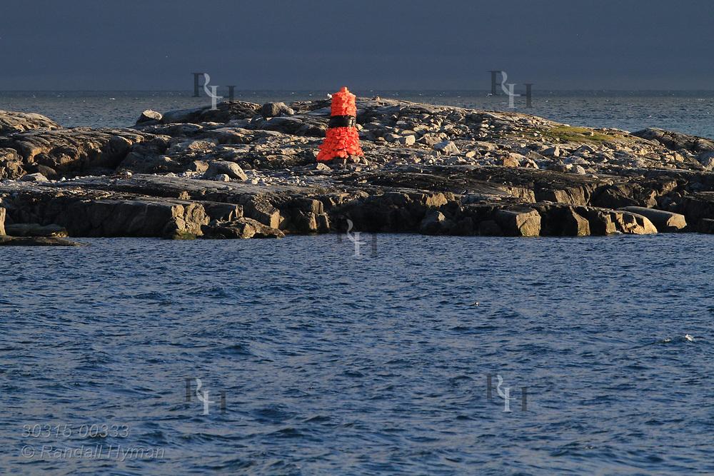 Orange navigational marker made of stones warns mariners entering Smeerenburgfjorden along north coast of Spitsbergen island; Svalbard, Norway.