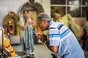 22 DECEMBER 2012 - SINGAPORE, SINGAPORE:   A man prays at the Sri Veeramakaliamman Temple, a Hindu temple located in Little India in Singapore. The Sri Veeramakaliamman Temple is dedicated to the Hindu goddess Kali, fierce embodiment of Shakti and the god Shiva's wife, Parvati. Kali has always been popular in Bengal, the birthplace of the labourers who built this temple in 1881. Images of Kali within the temple show her wearing a garland of skulls and ripping out the insides of her victims, and Kali sharing more peaceful family moments with her sons Ganesha and Murugan. The building is constructed in the style of South Indian Tamil temples common in Tamil Nadu as opposed to the style of Northeastern Indian Kali temples in Bengal.     PHOTO BY JACK KURTZ