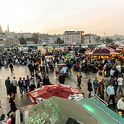 Eminonu watefront in Istanbul at dusk. On the banks of the Golden Horn next to the Galata Bridge is a popular place to get grilled fish sandwiches, cooked on the boats bobbing on the water next to the dock.