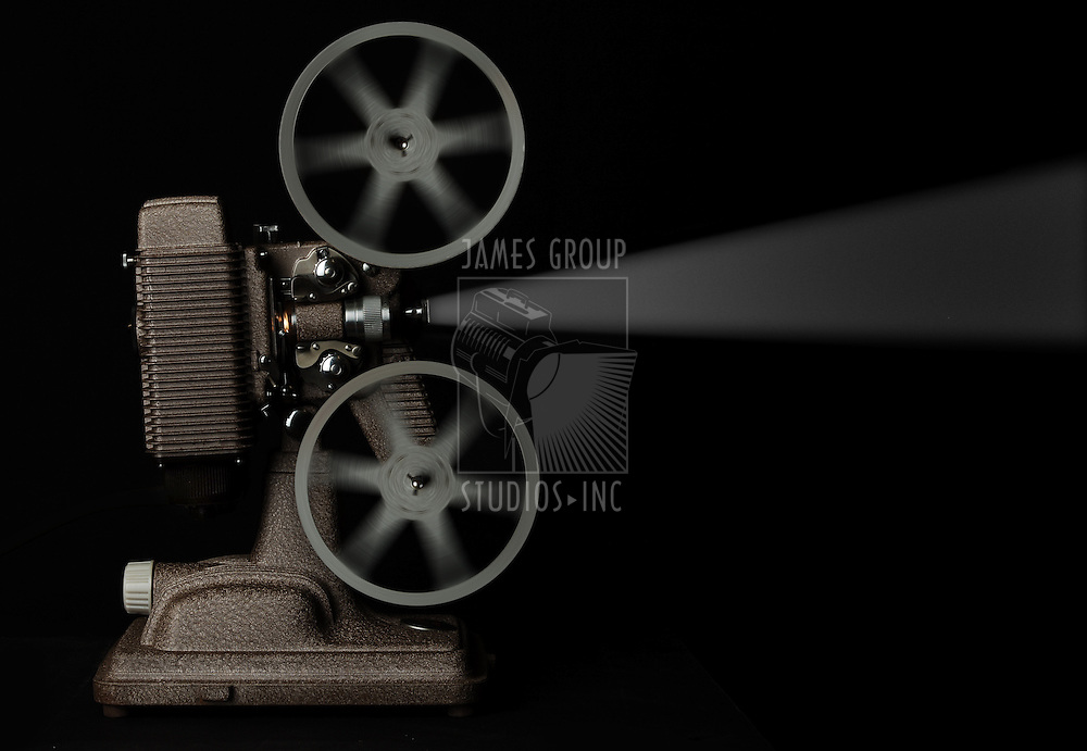 vintage movie projector running against dark background