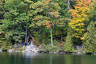 "Hikers relaxing along the shoreline of Pink Lake (Lac Pink) near the Pink Lake Trail.  Photographed during the ""Fall Rhapsody"" festival celbrating fall foliage colours in Gatineau Park, Québec, Canada."