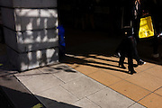 A Selfridges shopper with the branded yellow bag walks past the shadowy Ritz words on a street pillar.