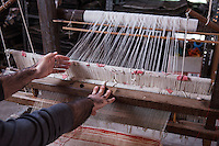 """SOVERIA MANNELLI, ITALY - 17 NOVEMBER 2016: Emilio Salvatore Leo (41), entrepreneur and heir of the woolen mill and historic family business Lanificio Leo, works on an antique horizontal loom in Soveria Mannelli, Italy, on November 17th 2016.<br /> <br /> Lanificio Leo was the first and last machine-operated woolen mill of Calabria, founded in 1873, it employed 50 people until the 1970s, when national policies to develop Italy's South cut out small businesses and encouraged larger productions or employment in the public administration.<br /> <br /> The woolen mill was on stand-by for about two decades, until Emilio Salvatore Leo, 41, started inviting international designers and artists to summer residencies in Soveria Mannelli. With their inspiration, he tried to envision a future for his mill and his town that was not of a museum of the past,<br /> Over the years, Mr. Leo transformed his family's industrial converter of Calabrian wool into a brand that makes design products for home and wear. His century old machines now weave wool from Australia or New Zealand, cashmere from Nepal and cotton from Egypt or South America. He calls it a """"start-up on scrap metals,"""" referring to the dozens of different looms that his family acquired over the years.<br /> <br /> Soveria Mannelli is a mountain-top village in the southern region of Calabria that counts 3,070 inhabitants. The town was a strategic outpost until the 1970s, when the main artery road from Naples area to Italy's south-western tip, Reggio Calabria went through the town. But once the government started building a motorway miles away, it was cut out from the fastest communications and from the most ambitious plans to develop Italy's South. Instead of despairing, residents benefited of the geographical disadvantage to keep away the mafia infiltrations, and started creating solid businesses thanks to its administrative stability, its forward-thinking mayors and a vibrant entrepreneurship numbering a national, medium"""