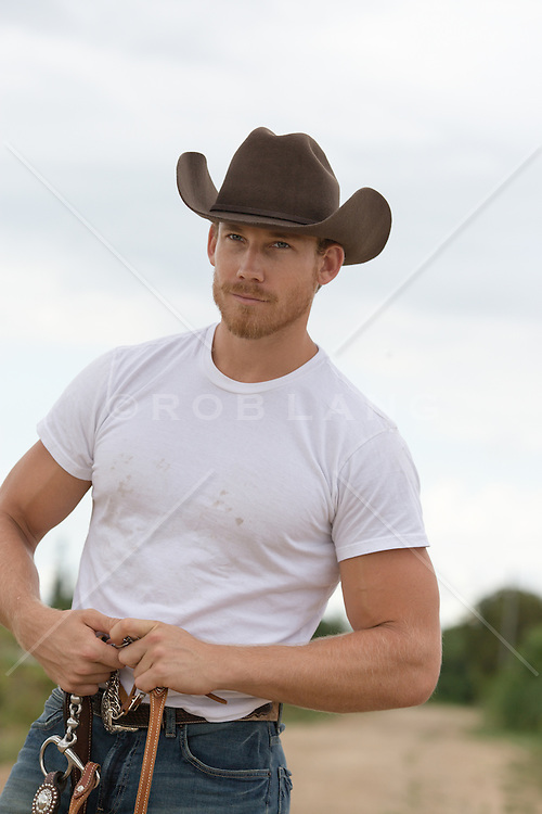 sexy cowboy holding reins on a dirt road