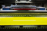 SOVERIA MANNELLI, ITALY - 17 NOVEMBER 2016: Yellow, magenta, cyan and black printing rolls are seen here in the Rubbettino Publishing House in Soveria Mannelli, Italy, on November 17th 2016.<br /> <br /> Rubbettino Publishing House, founded by Rosario Rubbettino in 1973, is of the largest publishing and printing houses in Italy's South. To abate logistical costs and make sure of the production quality, Rubbettino Publishing House built an integrated cycle inside its large warehouse inside Soveria Mannelli. Over 80 employees edit, print and package 300 new books a year for the Italian market, generating a turnover of 8 million euros.<br /> <br /> Soveria Mannelli is a mountain-top village in the southern region of Calabria that counts 3,070 inhabitants. The town was a strategic outpost until the 1970s, when the main artery road from Naples area to Italy's south-western tip, Reggio Calabria went through the town. But once the government started building a motorway miles away, it was cut out from the fastest communications and from the most ambitious plans to develop Italy's South. Instead of despairing, residents benefited of the geographical disadvantage to keep away the mafia infiltrations, and started creating solid businesses thanks to its administrative stability, its forward-thinking mayors and a vibrant entrepreneurship numbering a national, medium-sized publishing house, a leading school furniture manufacturer and an ancient woolen mill.