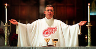 "Story:  Father Patrick Casey has a custom-made Detroit Red Wings vestment, made by a parishioner,  to wear during the hockey team's play-off run.<br /> Date: May 4, 2002<br /> Caption:  Reverend Patrick Casey (cq), age 38, celebrates mass saturday at Saint Dominic's, located at Trumbull and W. Warren, in Detroit, wearing a custom made Red Wings chasuble, the outermost vestment, in support of his favorite team.  ""May the Red Wings continue to do well and inspire our city to go beyond itself,"" he said during the prayers of the faithful.  Father Pat, who was born and raised in Waterford, got his first taste of ice hockey while serving in the Navy in Philadelphia in 1984.  A friend from Chesterfield Township made the vestment for father Pat in return for his leading the faithful on a pilgrimage to Medjugorje (cq), in the former Yugoslavia, earlier this year.  ""I did it to help get free playoff tickets and to draw attention to my two struggling inner city parishes,"" he said."