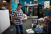 Joe Riofrio looks over bills in his closed store, the Westside Grocery in Mendota, Calif., September 10, 2012.