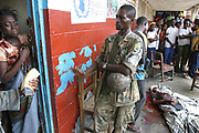 A Liberian government soldier stops a destraught woman from comming to see the body of a relative after being killed by a mortar bomb at the Newport High School, Monrovia 25 July 2003. Many civilians were wounded and killed after an early morning mortar attack from LURD(Liberians United fro Reconciliation and Democracy) rebels whose mortars landed in the High school compound which is home to hundreds of internally displaced peoples. Mortars have been landing all around the Mamba point district of the city this morning.This is the seventh day of fighting for the capital of Monrovia.<br /> EPA PHOTO/NIC BOTHMA