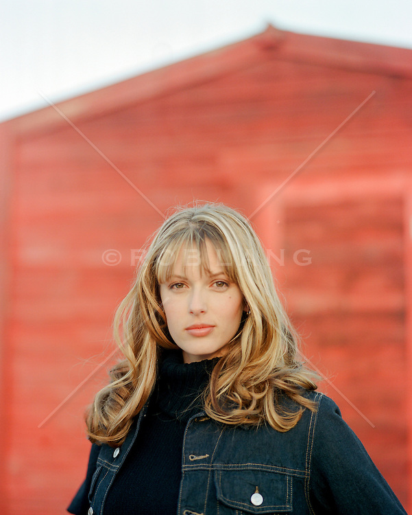 beautiful All American woman outdoors in a jean jacket by a red barn