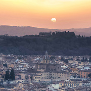 Shot from the top of the Duomo in Florence as early evening sunlight brings an orange glow to the city