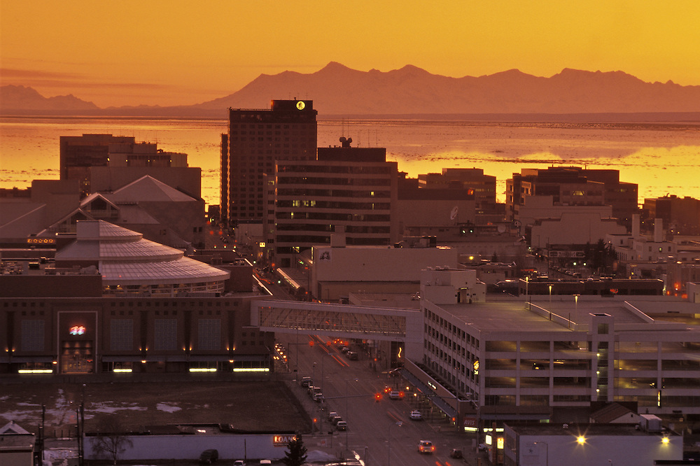 Twilight features a backdrop of Cook Inlet and the Alaska Range while man-made lights begin to illuminate the downtown Anchorage  streets.