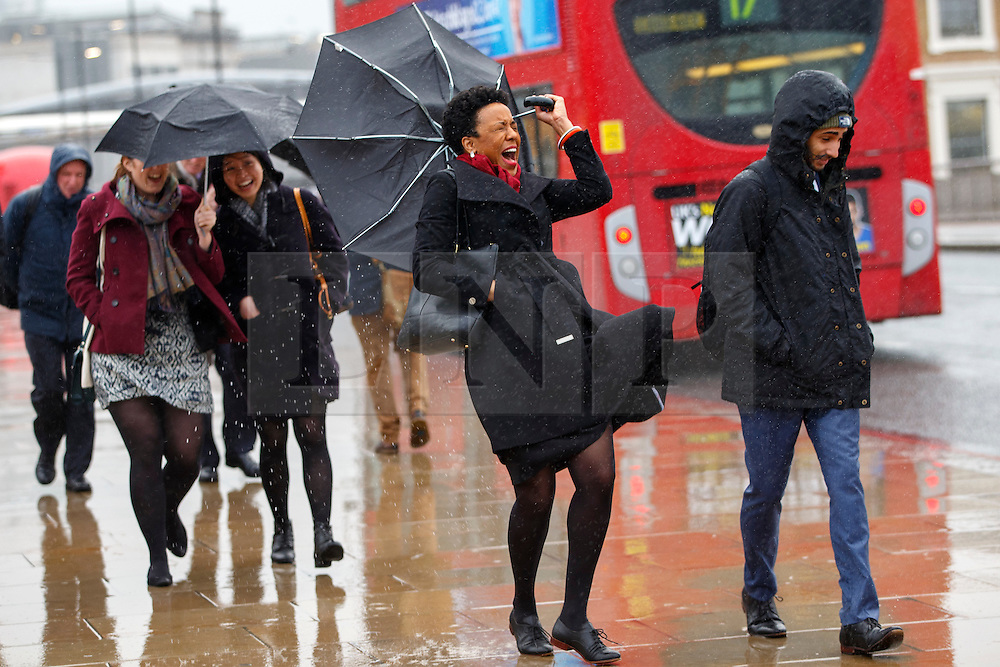 © Licensed to London News Pictures. 07/01/2016. London, UK. A commuter trying to hold on to her umbrella during a heavy rain on London Bridge in London on Thursday, 7 January 2016. Photo credit: Tolga Akmen/LNP