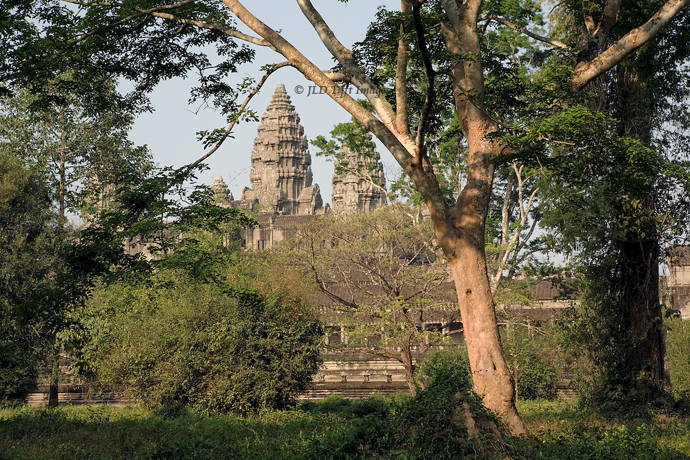 Angkor Wat : view from the  east just after dawn, seen from the surrounding forest of trees and shrubbery.  The tallest tower dominates the scene.