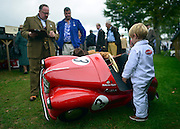 © Licensed to London News Pictures. 13/09/2013. Chichester, UK Harry Dark aged 4, from Oxfordshire, has his pedal car checked for suitability to be in the Paddock. People enjoy the atmosphere at the 2013 Goodwood Revival. The event recreates the glorious days of motor racing and participants are encouraged to dress in period dress. The revival is the only event of its kind to be staged entirely in the nostalgic time capsule of the 1940s, 50s and 60s Photo credit : Stephen Simpson/LNP.