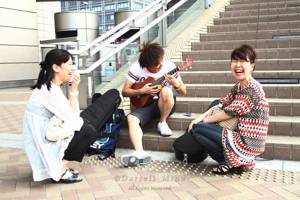 "Aug. 14, 2010 ; Osaka, JPN -  Shige Kobayashi, ukulele player on steps, Yuko Kosaka (right) from Kobe and Sachiko Uchida (left) from Takarazuka-shi outside Namba Hatch waiting for the doors to open for the Jake Shimabukuro ""I Love Ukulele Tour 2010"".."