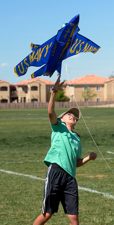 gbs041817a/ASEC -- Liam Simons, 12, of Albuquerque, throws a Navy jet kite into the air as his brother Caleb, 15,  tries to kept it aloft, but there wasn't enough breeze as they play in Vista del Norte Park on Tuesday, April 18, 2017. (Greg Sorber/Albuquerque Journal)