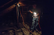 Mike Lehman from the Coporation for Appalachian Development (COAD) inspects the attic at 47 West Washington Street during an energy audit on Tuesday, June 23, 2015.  Photo by Ohio University  /  Rob Hardin