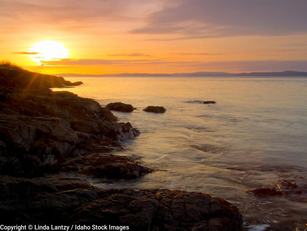 Washington, Fidalgo Island, Anacortes. Sunset over Puget Sound from Washington Park seashore rocks.