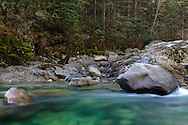 Large boulders in the emerald water of Gold Creek in Golden Ears Provincial Park near Maple Ridge, British Columbia, Canada.  The colour here is from minerals suspended in Gold Creek's water from its journey down from the Coast Mountains.  Photographed from along the North Beach Trail to the mouth of Gold Creek at Alouette Lake.