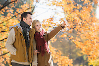 Woman pointing while standing with man in park during autumn
